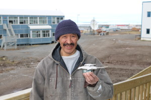 Roy, a resident of the small town of Kugluktuk, brings by a carving he made of two narwhals made out of soapstone. He has been carving for the past 30 years. (Photo credit: John Kelly)