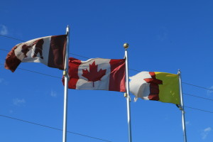 Three flags fly outside of the Hamlet office in Kugluktuk. From the left, the Kugluktuk flag, the Canadian flag, and the Nunavut flag. (Photo credit: John Kelly)