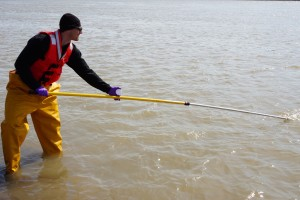 Researcher Matt Alkire uses a telescoping pole to collect water from the river. (Photo credit: Rob Macdonald)